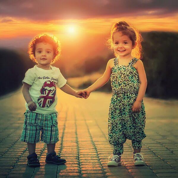 para dzieci w zachodzącym słońcu
